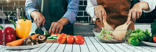 Obraz Two young asian couples are helping each other and enjoying cooking in the kitchen. - fototapety do salonu