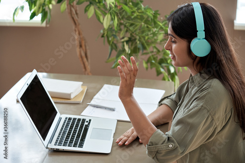 Fototapeta Happy indian teen girl student remote teacher tutor wear headphones giving online teaching class by webcam video call in zoom lesson looking at laptop virtual conference meeting work at home office