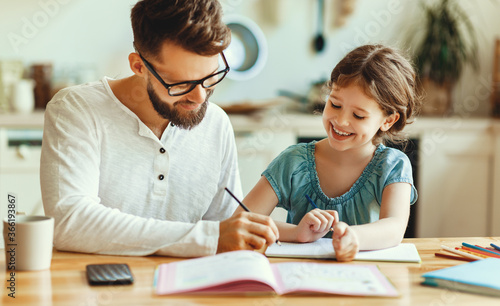 Fototapeta Father helping daughter with homework.