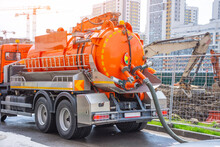 Pumping Water From Sewage Canals During The Construction Of Roads In The City. Truck With Orange Water Tank.