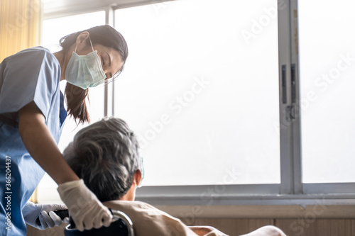 Fotografie, Obraz Asian nurse taking care of mature male patient sitting on wheelchair in hospital