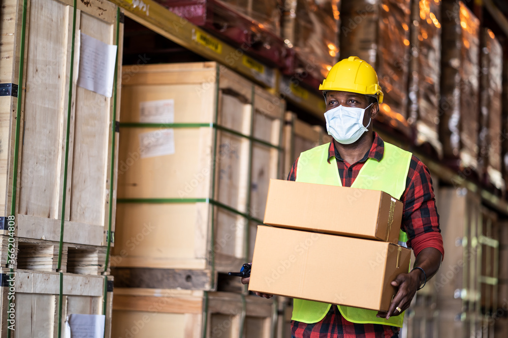Fototapeta Black male workers wearing protective face mask working in warehouse.