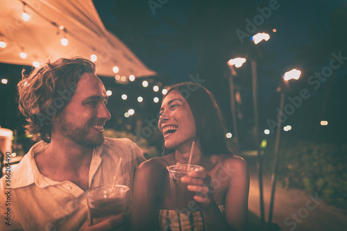Outdoor bar people drinking cocktails going out at night friends laughing dating couple happy lifestyle.