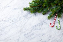 Christmas And New Year Decoration, Fir Tree And Candy Canes. Marble Background. Copy Space. Top View.