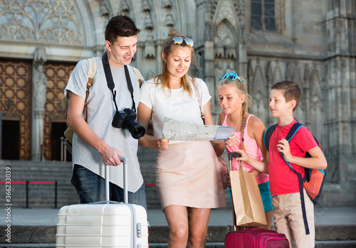 Young happy parents with two kids traveling together searching location on paper Wallpaper Mural
