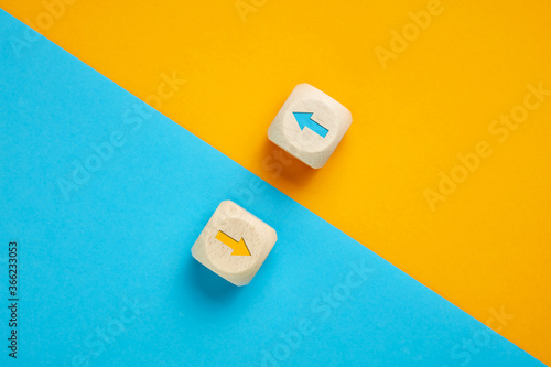 Fotografie, Obraz Arrow icons in contrast on wooden cubes moving towards opposite directions