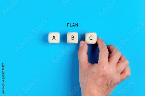 Fototapeta Male hand choosing business plan c out of three options obraz