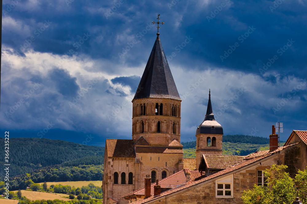 Fototapeta entrée de l'Abbaye de Cluny, avec une ciel menaçant sur les collines environnantes