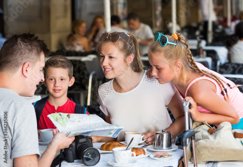Photo Cheerful parents with two kids relaxing in cafe searching location on map