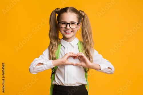 Smiling schoolgirl gesturing heart shape with fingers on yellow background Fototapeta