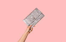Young Woman Showing Silver Sparkly Clutch Bag On Pink Background, Closeup
