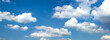 canvas print picture - Wide banner with blue sky and white clouds.