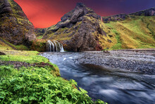 Wonderful Nature Of Iceland. Fresh Green Grass And Icelandic Moss Near River With Waterfall. Tipical Icelandic Scenery During Sunset. Dramatic Scene Of Stjornarfoss Waterfall With Colorful Sky