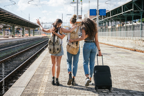 Three young friends women at the station walking and waiting train for their tri Fototapeta