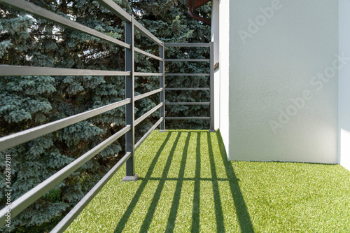 Leinwand Poster balcony railing with a synthetic grass