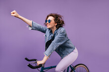 Confident Girl In Denim Jacket Riding On Bike And Waving Hand. Indoor Photo Of Inspired Young Lady In Glasses Sitting On Bicycle.