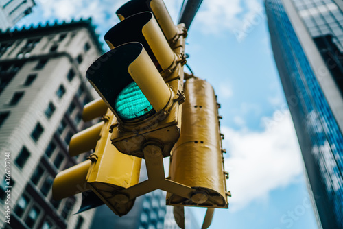 Green light lamb on equipment for controlling transport on intersection in downtown, traffic light hanging over avenue in New York city supporting safety on crossing in district with high buildings.