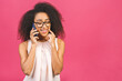 canvas print picture - Portrait of a cute happy afro american black girl in casual talking on mobile phone and laughing isolated over pink background.