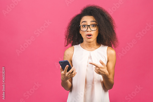 Fotografie, Obraz Attractive curly dark skinned american female with Afro hairstyle looks agitated at screen of smart phone, impressed by message content recieved from friend, has surprised facial expression
