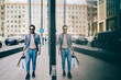 Happy stylish young man with beard strolling in urban setting and enjoying shopping in trendy stores in modern city.Positive cool hipster guy with paper bags walking near showcase with reflection