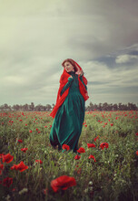 A Girl In Vintage Clothes Stands On A Poppy Field With A Cape On Her Head