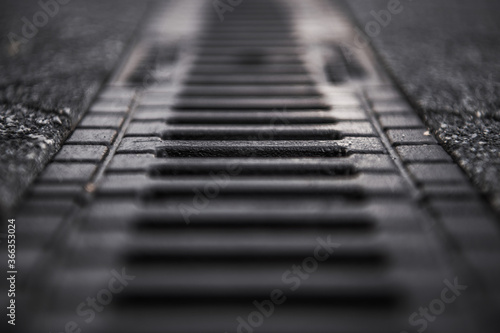 Obraz Street and Driveway Storm Water Drain Close Up with Shallow Depth of Field. Infrastructure Element Designed to Drain Excess Rain. - fototapety do salonu