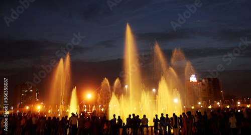 A large number of city peoples enjoying coolness in front of a fountain due to h Wallpaper Mural