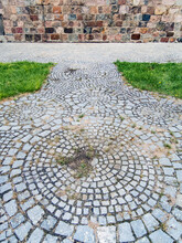 Old Gray Circular Paving Stones, Green Grass And Colourful Stone Wall, Czerwińsk, Poland