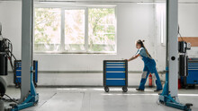 African American Woman, Professional Female Mechanic Pulling, Carrying Tool Box Cart In Auto Repair Shop. Car Service, Maintenance And People Concept