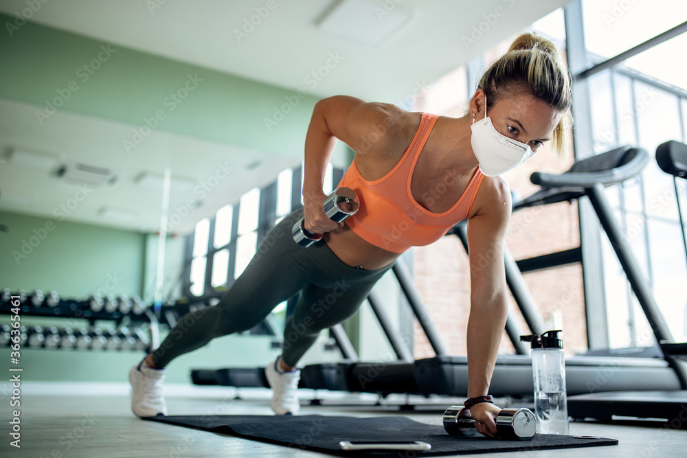 Fototapeta Female athlete with protective face mask doing plank exercise with hand weights in a gym.