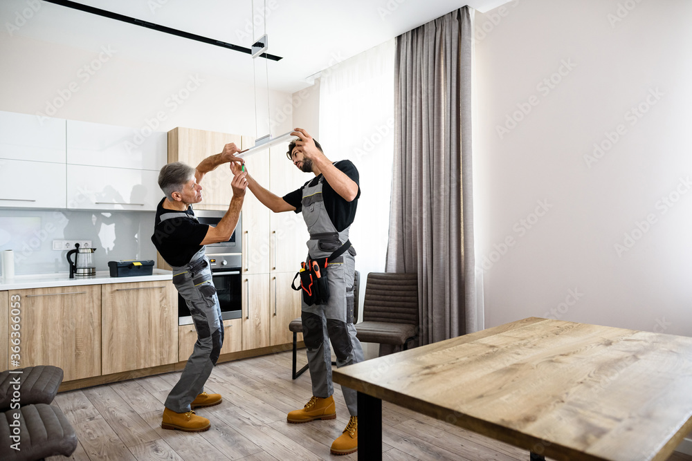 Fototapeta Full length shot of two electricians, workers in uniform installing electric lamp, light inside apartment in the kitchen. Construction decoration concept