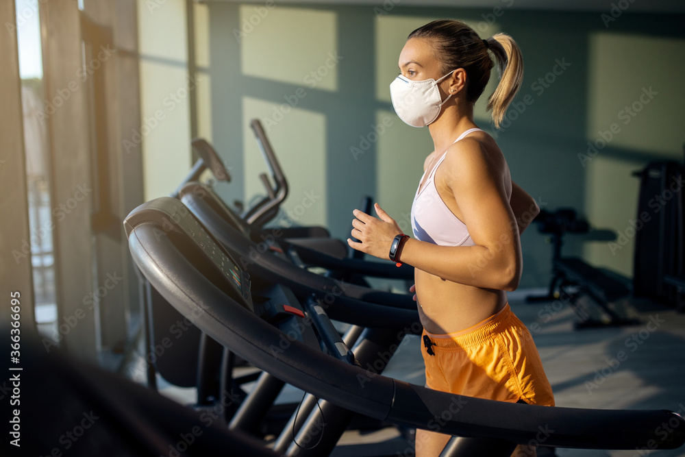 Fototapeta Athletic woman with face mask running on treadmill in health club.