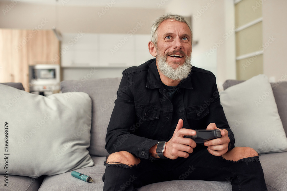 Fototapeta Up to the challenge. Bearded middle-aged man holding controller, playing video games, sitting on the couch at home. Weed vaporizer, dry herb vape pen lying next to him