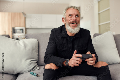 Obraz Up to the challenge. Bearded middle-aged man holding controller, playing video games, sitting on the couch at home. Weed vaporizer, dry herb vape pen lying next to him - fototapety do salonu