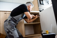 Aged Repairman In Uniform Working, Fixing Kitchen Cabinet Using Screwdriver. Repair Service Concept