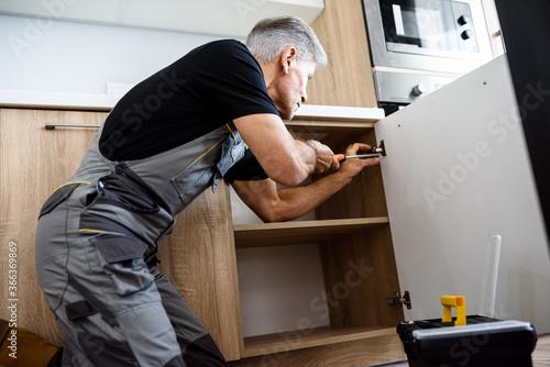 Fototapeta Aged repairman in uniform working, fixing kitchen cabinet using screwdriver