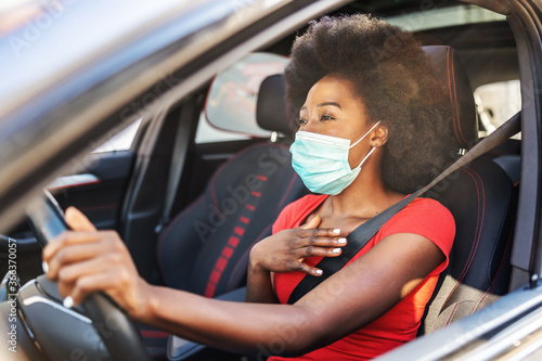 Obraz Young attractive african woman with mask on her face driving her car during covid-19 pandemic. - fototapety do salonu