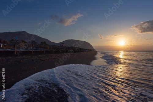 Fotografia Santorini - Black beach of Perivolos with a beautiful long wave of the sea, illuminated by the first rays of the sun at sunrise
