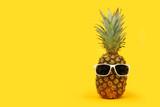 Fototapeta Kawa jest smaczna - Pineapple with sunglasses against a bold yellow background. Minimal summer concept.