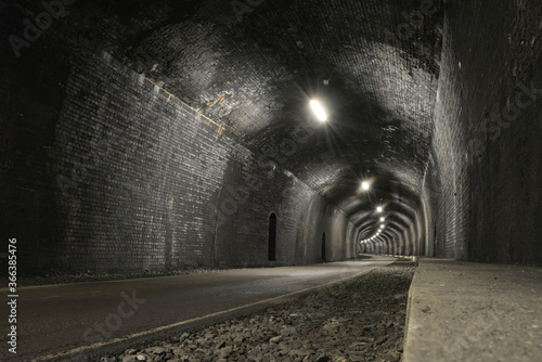 Fotografija Road passes through dark grey brick tunnel lit by bars of light.