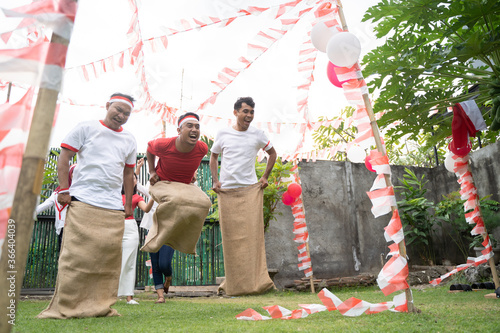 three young men happily joined in sack race jumping quickly to reach the finish Canvas-taulu