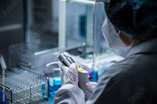Fototapeta ウィルス分析用の機械を手に取る研究者