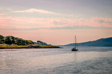 A Sail Boat Leaves Loch Aline Behind. Loch Aline Is A Small Salt Water Loch Home To Fish, Birds And Game, Located In Morvern, Lochaber, Scotland.