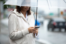 Asian Woman Is Using On Smartphone, Checking Social Media Network And Holding Umbrella While Waiting Taxi On The City Street In The Rainy Day.