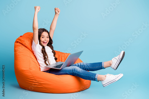 Obraz Portrait of nice attractive cheerful cheery excited glad wavy-haired girl sitting in chair using laptop celebrating win isolated on bright vivid shine vibrant blue teal turquoise color background - fototapety do salonu