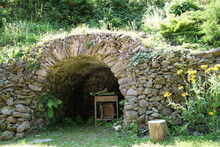 A Small Artificial Cave Built Out Flat Stones Layered Caefully Over Each Other.