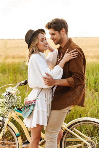Image of young couple hugging while riding bicycle in countryside