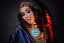 Beautiful American Indian Girl With Traditional Make Up In Indian Feather Hat And Ethnical Clothes. Studio Portrait With A Striped Shadow From The Blinds On A Dark Background