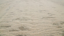 Small Dunes Of Gray-beige Grainy Sand Waves Going Into Perspective, The Surface Is Covered With Ripples On The Beach Of The Sea Coast. Natural Mineral Sand Background