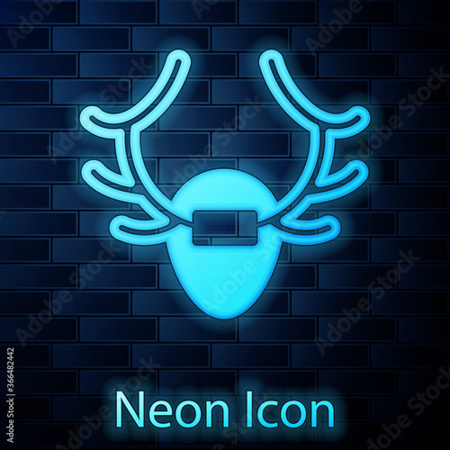 Glowing neon Deer antlers on shield icon isolated on brick wall background Canvas Print